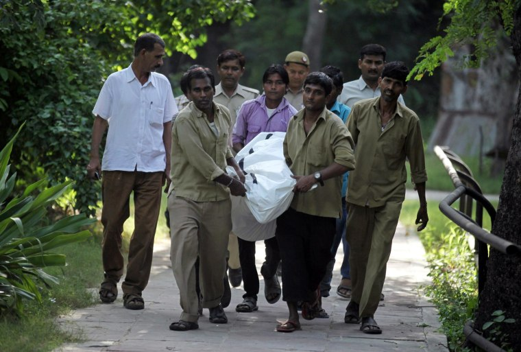 The body of a young man is removed after he was killed by a white tiger at the zoo in New Delhi on Sept. 23. The man climbed over a fence at the zoo and jumped into the animal's enclosure, a spokesman said.