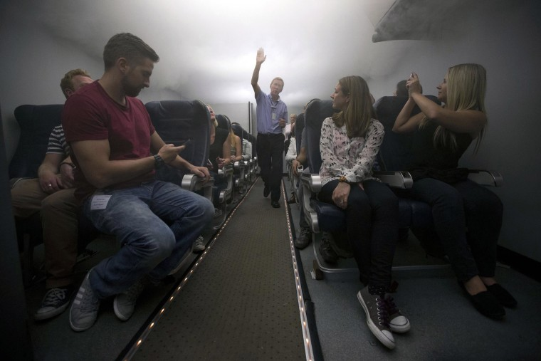 British Airways flight safety instructor Andy Clubb, center, instructs participants as theatrical smoke begins to fill the cabin simulator during a British Airways flight safety course at the airline's Cranebank training facility, near Heathrow airport in London, on Sept. 10.