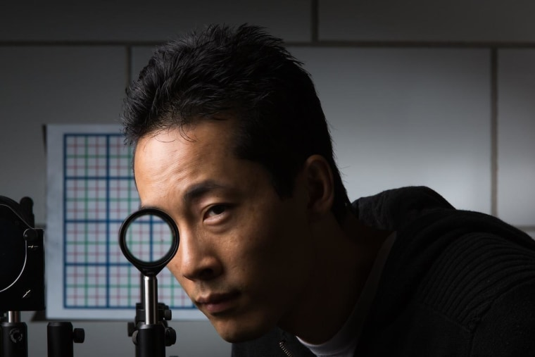 """University of Rochester researcher Joseph Choi hides part of his face in a """"perfect paraxial"""" cloaking device constructed from four lenses."""