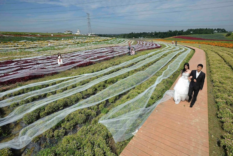 Promotional staff dressed as newly-weds walk along a path as they display a 4,100-meter-long wedding dress train during an event promoting a tourism valley near Chengdu, Sichuan province, Sept. 24, 2014.