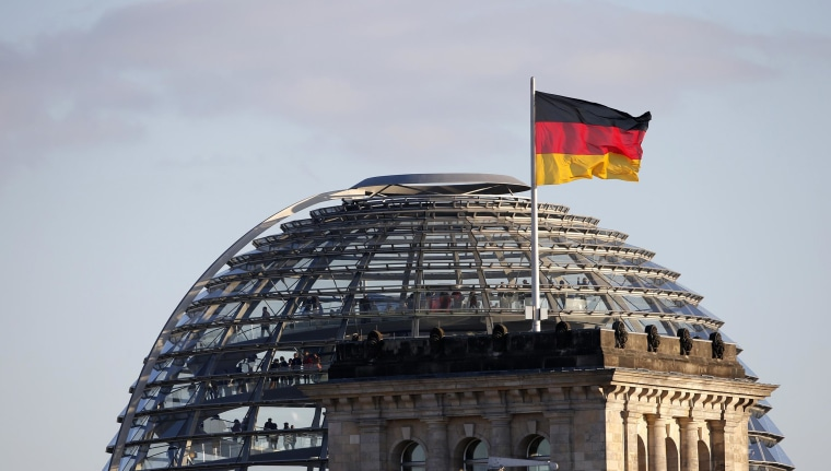 A German flag flutters next to the dome of the Reichstag building in Berlin