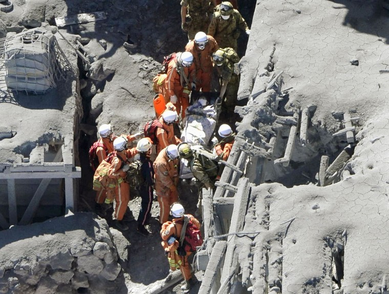 Image: JSDF soldiers and firefighters carry an injured person among mountain lodges, covered with volcanic ash, near a crater of Mt. Ontake, which straddles Nagano and Gifu prefectures