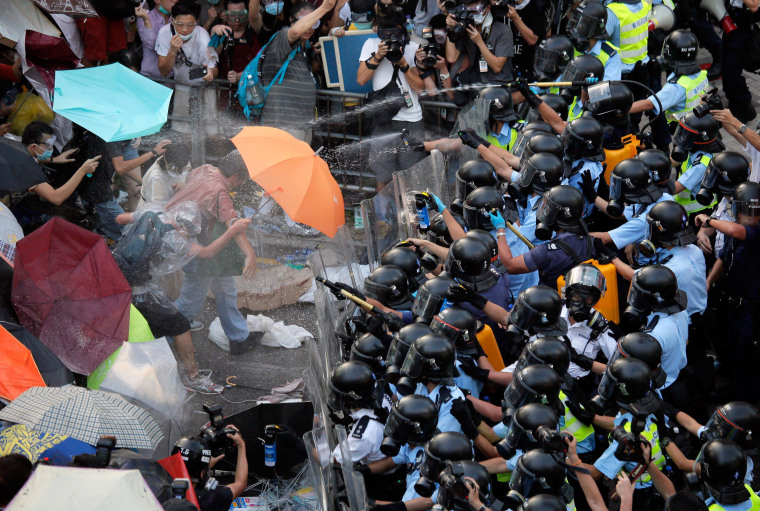 Image: Riot police use pepper spray against protesters