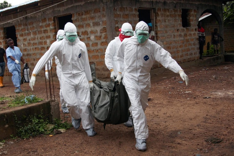 Image: Liberian nurses carry the body of an Ebola victim from a house for burial in the Banjor Community on the outskirts of Monrovia, Liberia