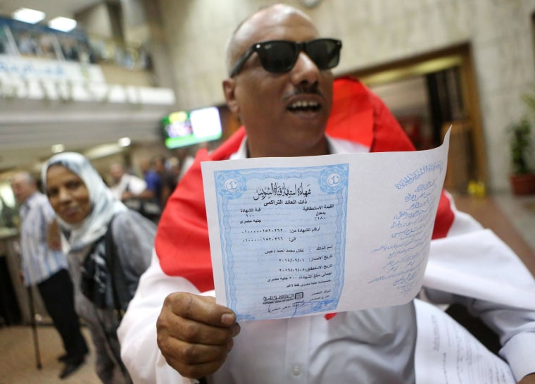 Image: Adel Mohammed Ahmed, wearing a national flag, holds an investment certificate used to finance the extension of the Suez Canal
