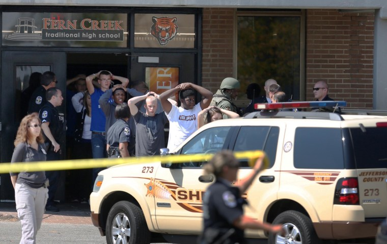 Image: Students put their hands on their heads as they are lead out of Fern Creek High School in Louisville, Ky