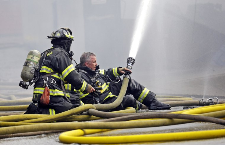 Image: A firefighter briefly goes without his helmet as he prepares to put on a mask while hosing down a building on fire