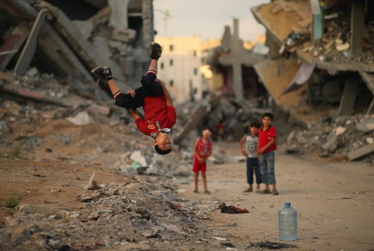 Image: A Palestinian boy practices his Parkour skills near the ruins of houses east of Gaza City