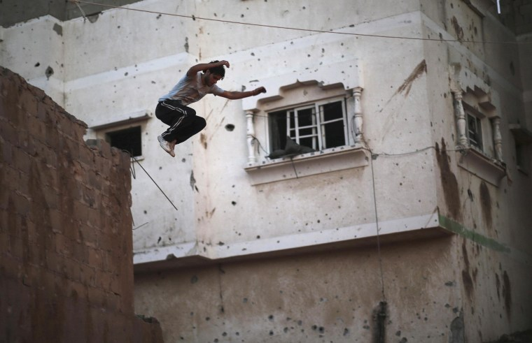 Image: A Palestinian youth jumps from a house as he practices his Parkour skills