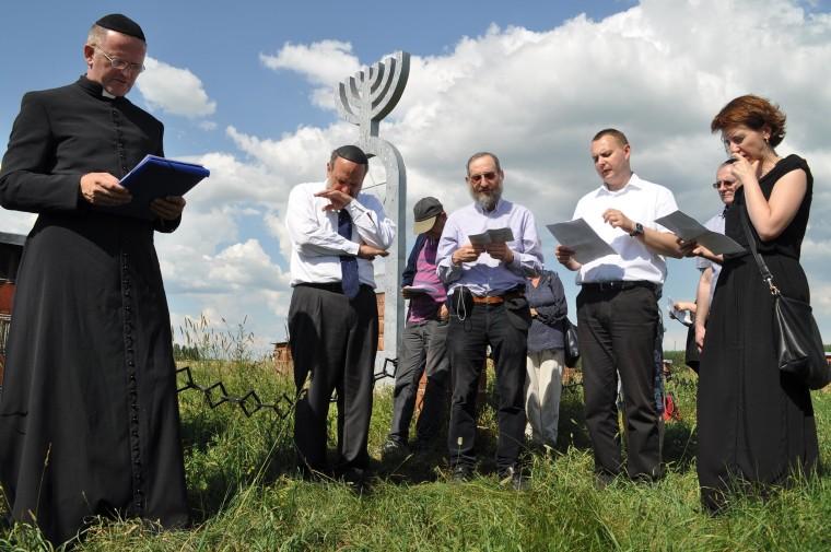 Priests and rabbis pray at the memorial at Wasosz, Poland.