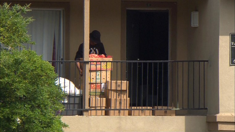 Image: Relatives of Ebola patient Thomas Duncan pick up foods delivered to their apartment in Dallas, They've been confined while officials assess their risk of infection