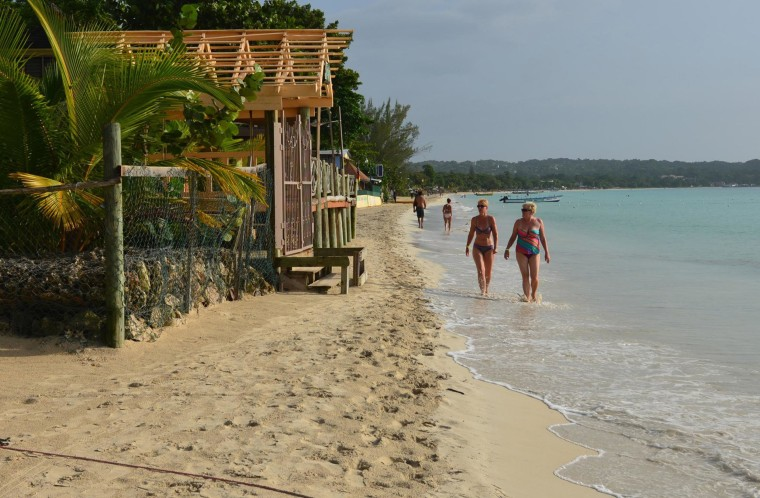 Image: Tourists walk along a badly eroding patch of resort-lined beach in Negril, Jamaica