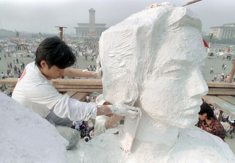 "Image: A Chinese student plasters the neck of the ""Goddess of Democracy"" in Tiananmen Square on May 30, 1989"