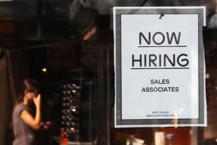 """Image: A \""""Now Hiring\"""" sign hangs on the door to the Urban Outfitters store at Quincy Market in Boston"""