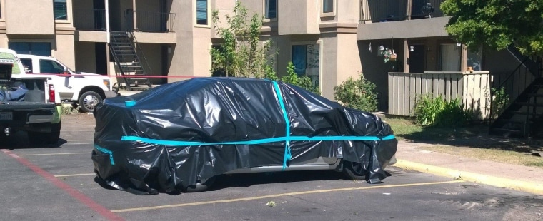 A car is wrapped in plastic Oct. 3 in the parking lot as a hazmat team prepared to clean the apartment in Dallas where Ebola patient Thomas Eric Duncan had been staying.