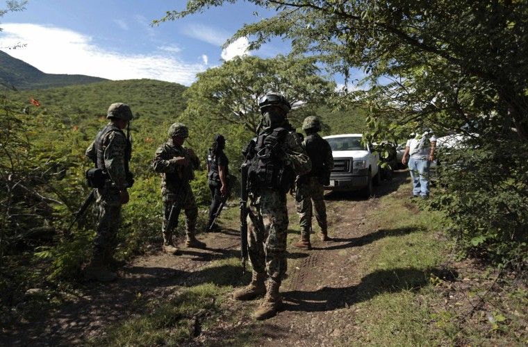 Image: Soldiers guard an area where a mass grave was found, in Colonia las Parotas on the outskirts of Iguala, in Guerrero