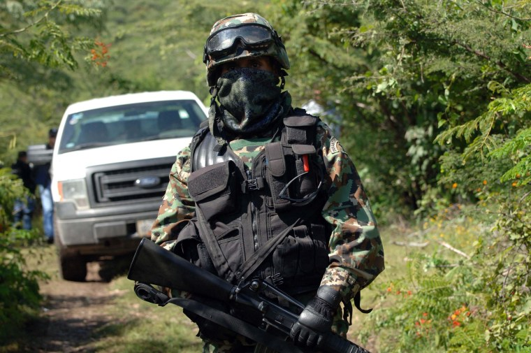 Image: A Mexican navy marine guards the road that leads to the site where an alleged clandestine mass grave was found