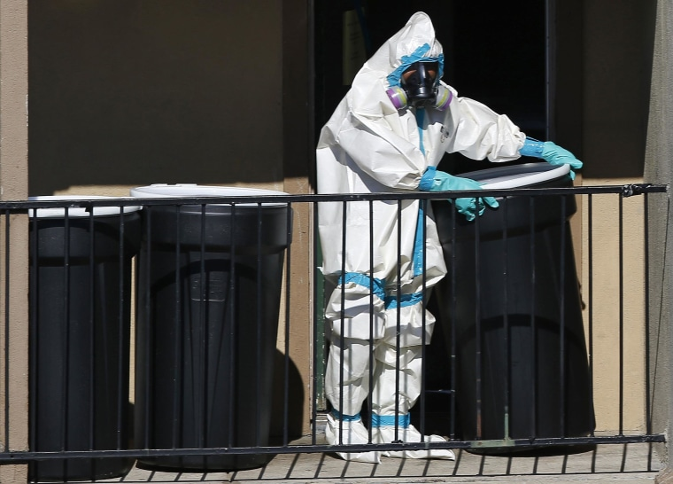 Image: A worker in a hazardous material suit rolls out barrels of contents from the apartment unit where a man diagnosed with the Ebola virus was staying in Dallas