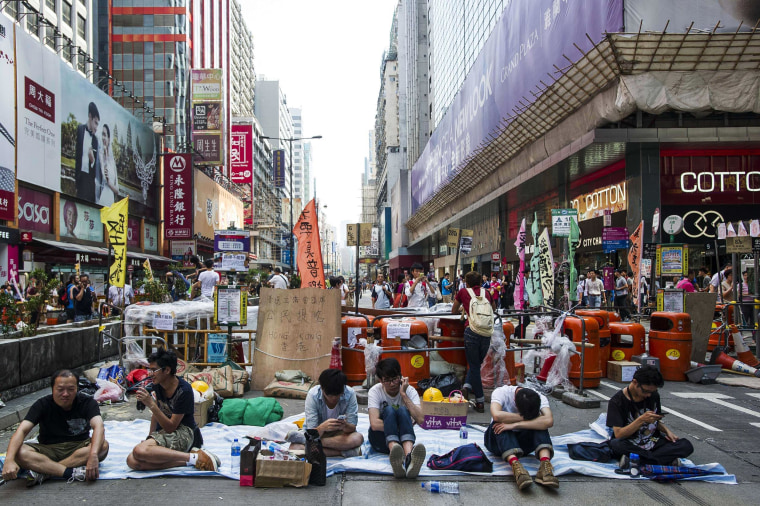 Image: Pro-democracy protesters sit in front of a barricade in the Mongkok district