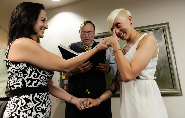 Image: Sen. Jim Dabakis marries Yolanda Pascua, left, and Laekin Rogers as she wipes away tears