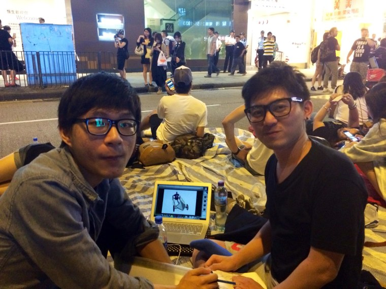 Sophomores Peter Chung, left, and Hugo Chan, both 21, work on a project for their Visual Communications course while taking part in the protests in Hong Kong.