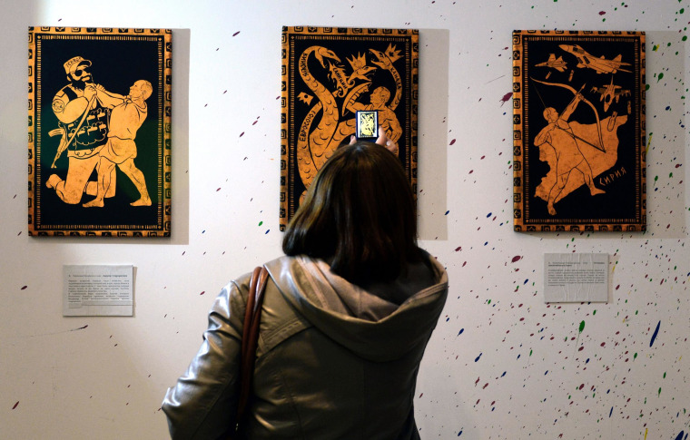 "A visitor takes photos of artwork in ""The 12 Feats of Vladimir Putin,"" art exhibition on Oct. 6, at a design workshop in Moscow."
