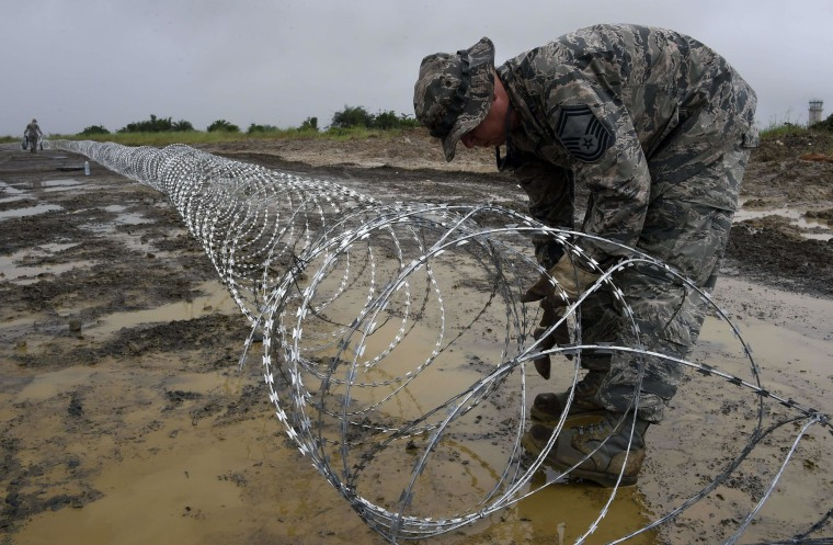 Image: Air Force personnel lay out barbed wire around the position for an Ebola treatment center in Monrovia, Liberia