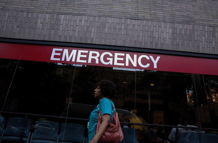 Image: A woman walks in front of a New York City hospital
