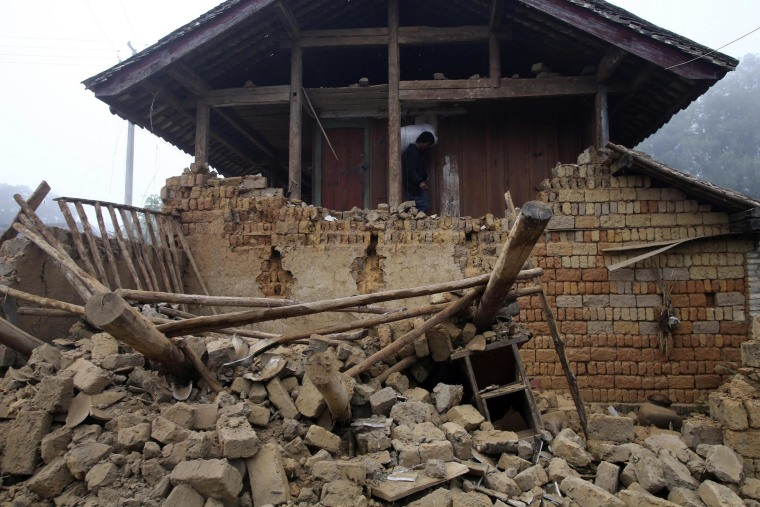 Image: A man carrying a bag walks past the ruins of a damaged house after an earthquake hit Yongping township of Jinggu county