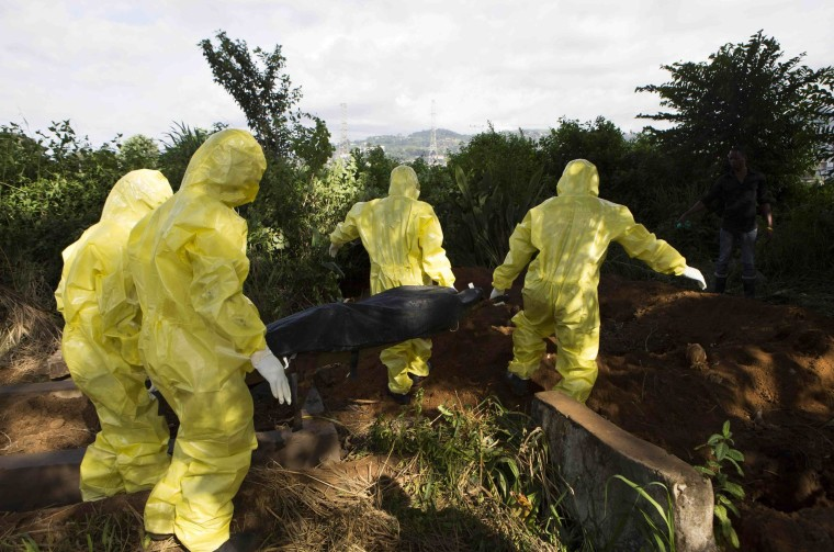 Image: Burial team prepares body of Ebola virus victim in Freetown, Sierra Leone