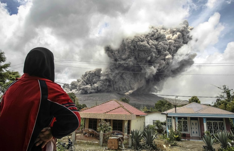 Image: Woman in a village in Karo regency watches Mount Sinabung erupt in Indonesia's North Sumatra province