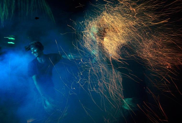 """Image: Balinese men lash burning coconut husks during """"Mesabatan Api,"""" in Bali on Wednesday."""