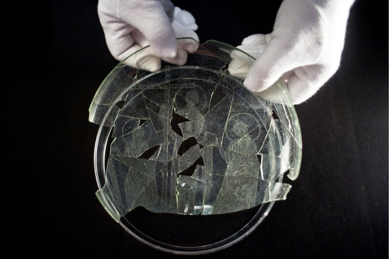 An employee in at the Museum of Archaeology of Linares shows off a glass dish that bears the engraved image of a short-haired Jesus without a beard, flanked by two haloed apostles thought to be Peter and Paul.