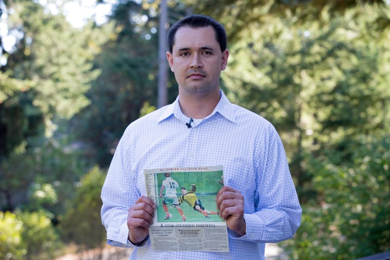 Casey Sullivan holds a photograph taken before he was diagnosed with stage 4 Hodgkin lymphoma. Sullivan, a former goalkeeper, wonders whether his time spent on crumb rubber artificial turf exposed him to harmful chemicals.