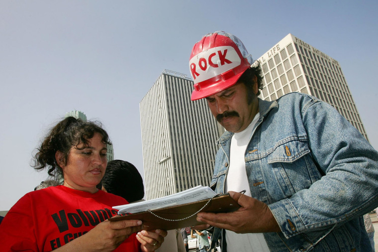 """File photo of a Los Angeles man signing petitions to then Senate Majority Leader Bill Frist and Speaker of the House Dennis Hastert calling for """"realistic and humane"""" immigration reform, as """"No on Proposition 187"""" organizers launch a voter registration and citizenship drive on May 19, 2006 in Los Angeles, California."""