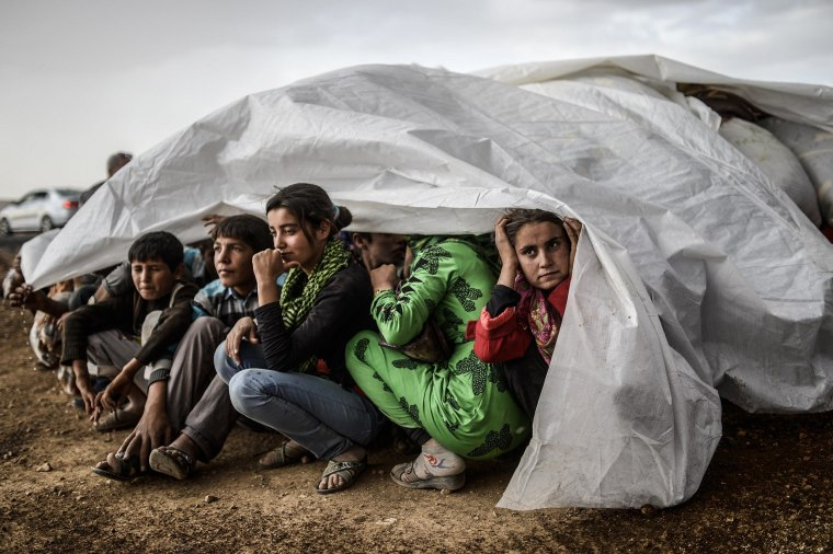 Image: Syrian Kurds take cover from the rain in the southeastern town of Suruc