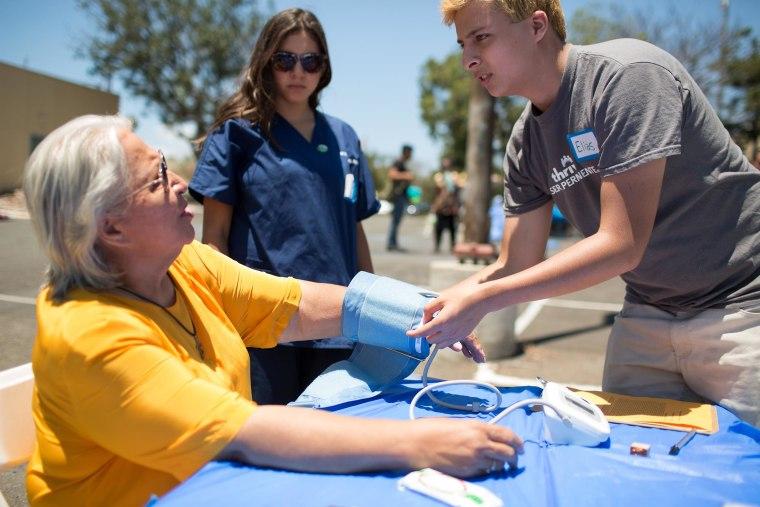 Image: Medical Pathways graduate Elias Preciado checks a patient's blood pressure