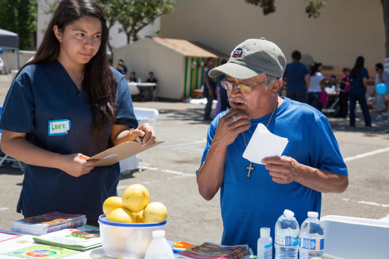 Image: Lorenia Gutierrez talks to a health fair patient about making good nutritional choices.