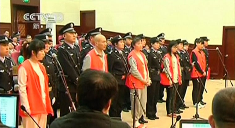 Image: Defendants stand with police escorts during their trial for the murder of a woman at a McDonald's restaurant, in Yantai City