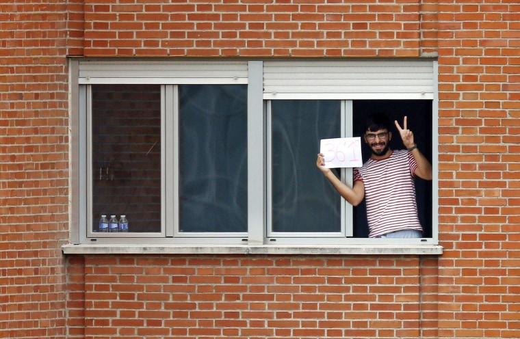 Image: Unidentified man gestures as he shows what is believed to be his body temperature from the window of his room at an isolation ward on the fifth floor at Madrid's Carlos III Hospital
