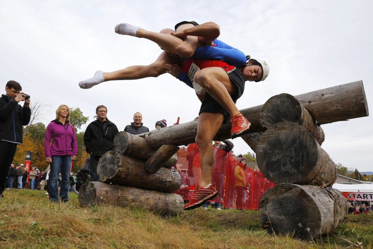 Image: Jeff and Kelly Lyons clear the first obstacle while competing in the North American Wife Carrying Championship at Sunday River ski resort in Newry
