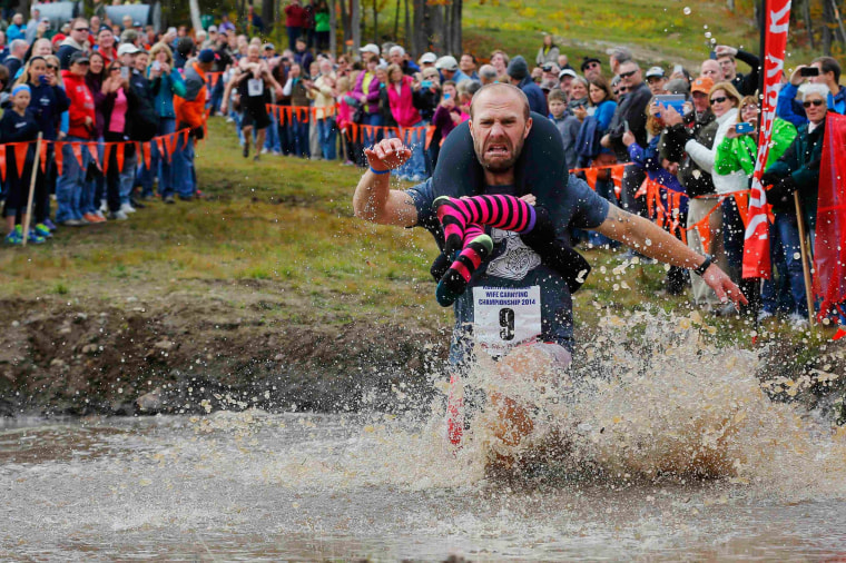 Image: Eventual winners Jesse Wall carries Christina Arsenault through the water pit while competing in the North American Wife Carrying Championship at Sunday River ski resort in Newry