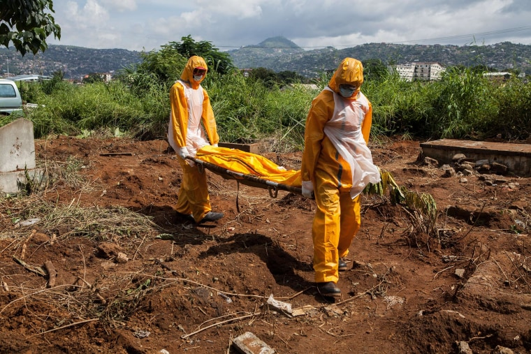 Image: A team of funeral agents specialized in the burial of victims of the Ebola virus carry a body prior to put it in a grave