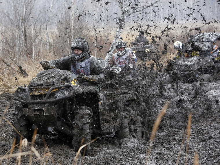 """Image: Riders compete during the """"Kings of the Off-road"""" quad bike amateur regional race in a Siberian boggy district near the village of Kozhany"""