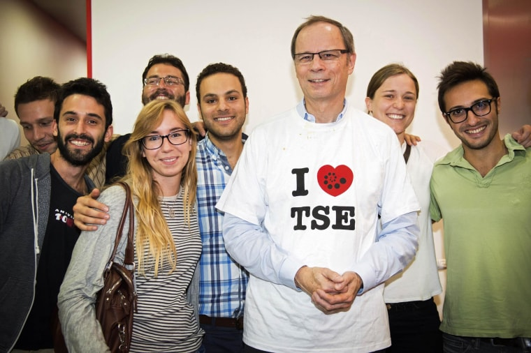 Image: French economist Jean Tirole poses with students after a news conference at the Toulouse School of Economics