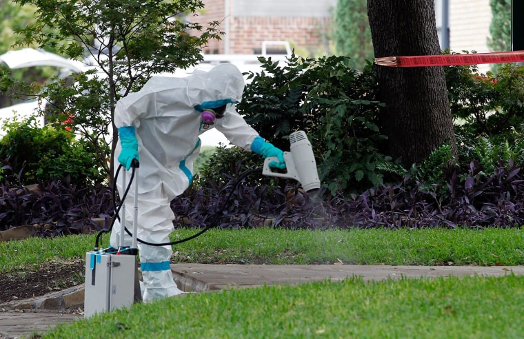 Image: A man dressed in protective hazmat clothing treats the sidewalk in front of an apartment where nurse Nina Pham resides