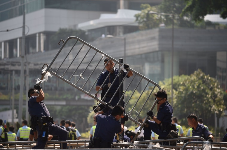 Police officers remove barricades of pro-democracy protestors in the Admiralty district of Hong Kong on October 14, 2014.