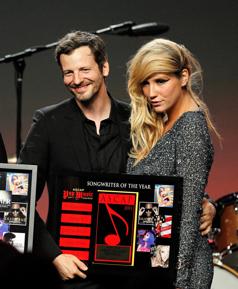 Songwriters Kesha and Lukasz Gottwald (2nd R), better known as Dr. Luke, accept an award in 2011.