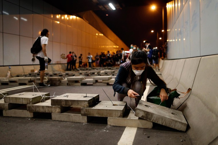 Image: A pro-democracy protester lays bricks inside a vehicle tunnel to block traffic leading to the financial Central district in Hong Kong