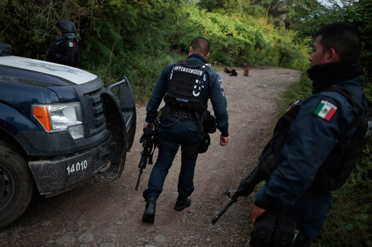 Image: Federal police walk on a road at an area near clandestine graves at Pueblo Viejo, in the outskirts of Iguala, southern Mexican state of Guerrero